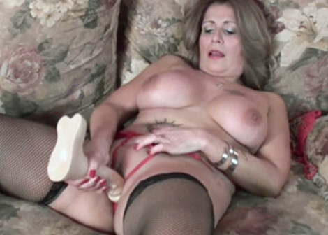 Busty cougar Sandie plays with a huge dong